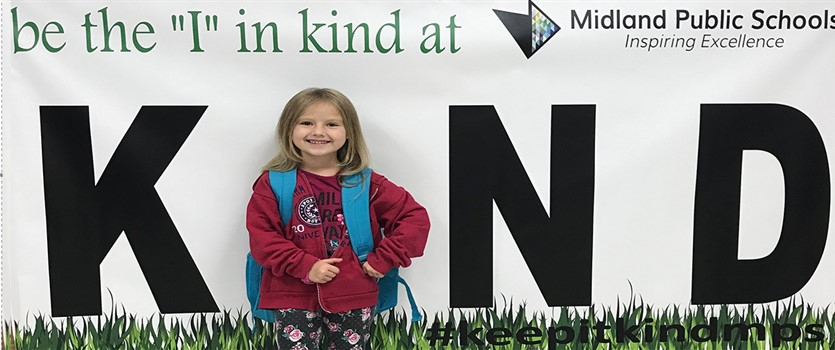 Student posing with keeping it kind banner